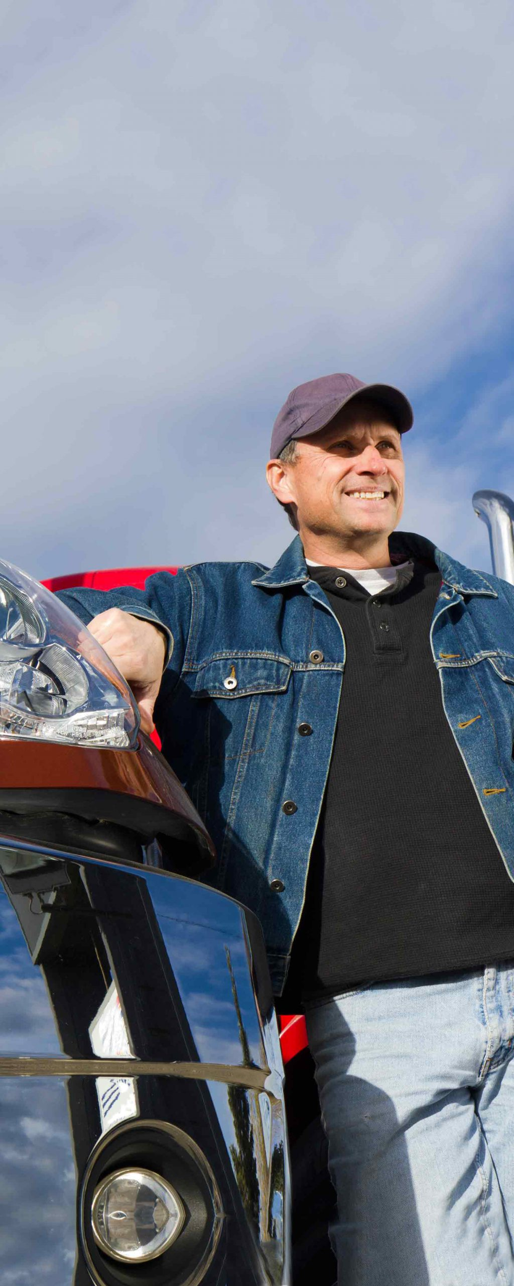 Tractor-trailer owner-operator leaning against leased truck in denim jacket and ball cap.
