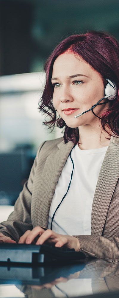 Young woman wearing headset working at computer to track insurance coverage.